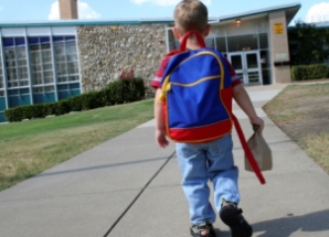 Child with backpack walking towards a school