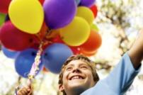 Boy in blue shirt holding bunch of coloured balloons