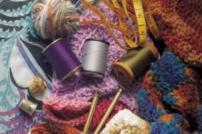 Photo of knitting needles and wool with cotton reels and tape measure