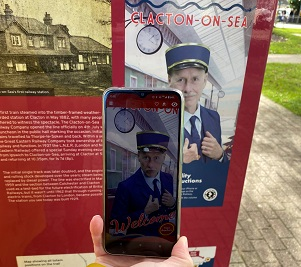 A mobile phone showing the AR in action at a Clacton 150 Heritage Trail board