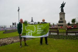 Open spaces team member Sean Biswell and Councillor Michael Talbot with a new Green Flag at Clacton seafront gardens