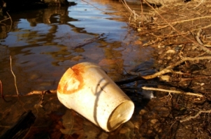 Photograph of a polysterene cup lying in a dirty stream