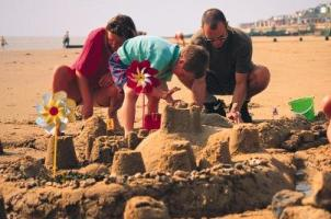 Photograph of a family building sandcastles