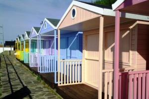 Row of eight pastel beach huts