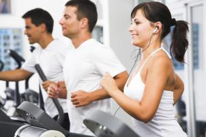 Men and lady using gym equipment
