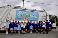 Amber Wheeler with other pupils who entered the competition, with the poster on a refuse lorry