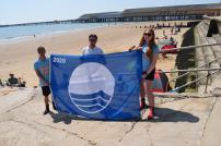 Walton Beach Patrol members (from left) Liam Noah, Marcus Russell and Jorden Gleave with the new Blue Flag for Walton