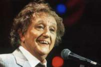 Head and shoulders photo of Ken Dodd on stage with microphone